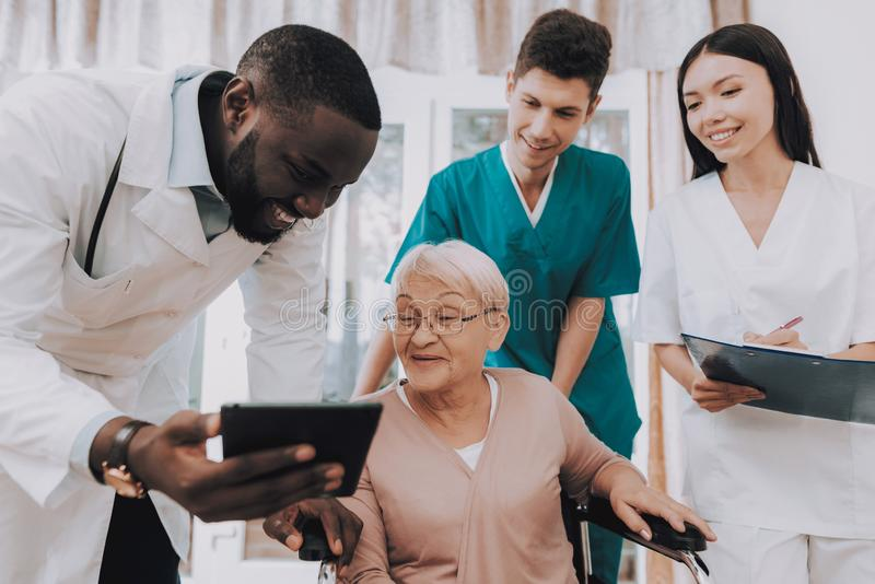 Doctor Show Test Results. Very Surprised Patient. Elderly Woman Looks in Hospital Case. Doctor with Tablet. Patient on Wheelchair. Nursing Home. Doctor in stock photography