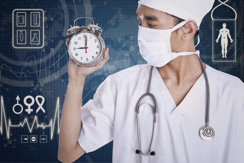 A doctor showing an alarm clock. With blue digital screen background stock images
