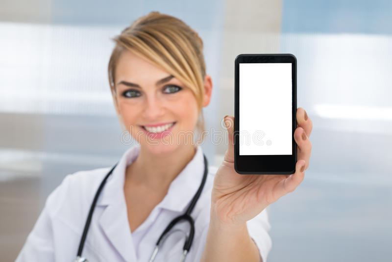Doctor showing cellphone. Portrait Of Happy Young Female Doctor Showing Cellphone stock image