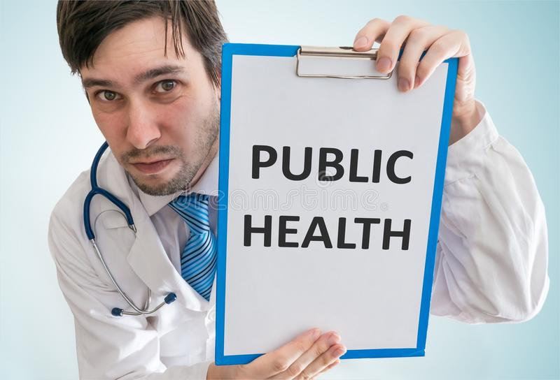 Doctor is showing clipboard with public health text written. View from top royalty free stock photo