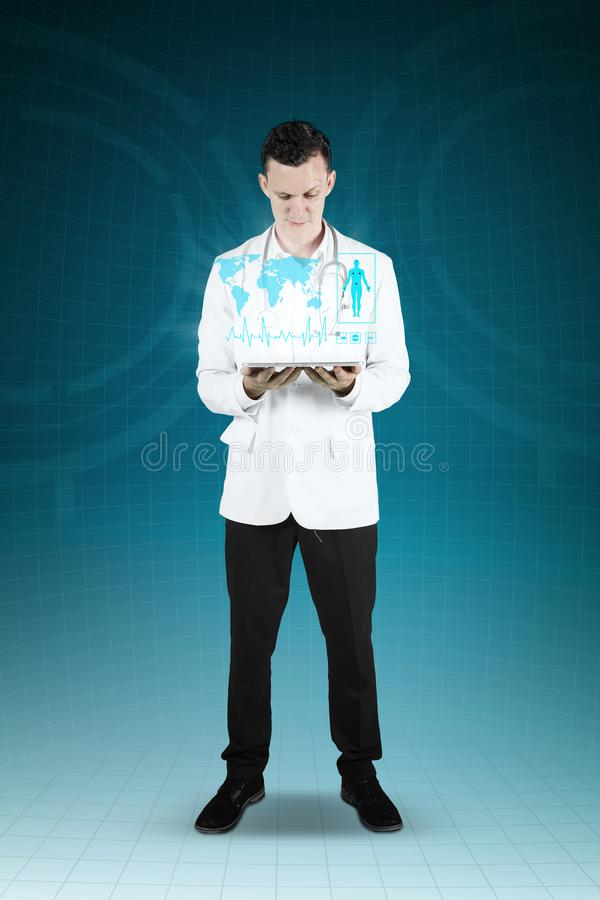 Doctor showing a digital tablet and medical symbol. Male Caucasian doctor showing a digital tablet and medical symbol. Shot with virtual screen background royalty free stock images