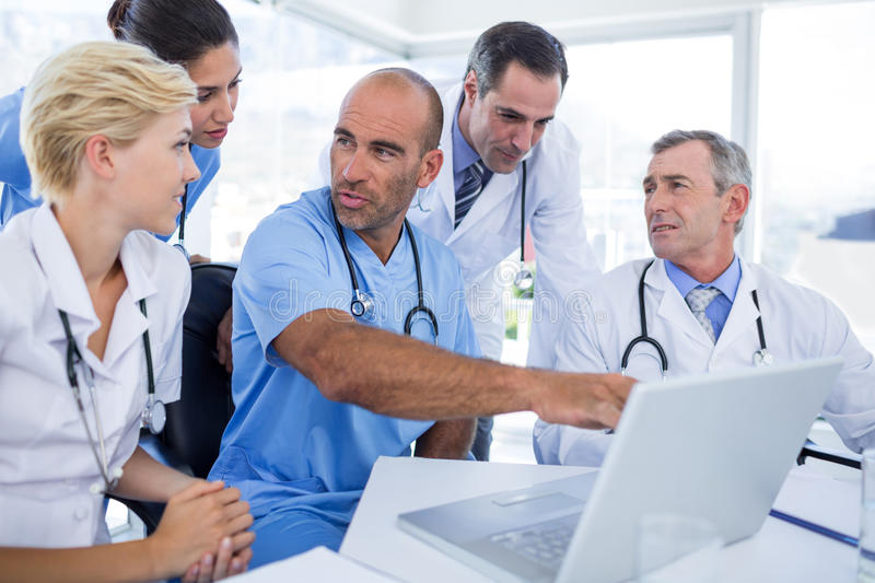 Doctor showing laptop pc to his colleagues. In medical office stock photo