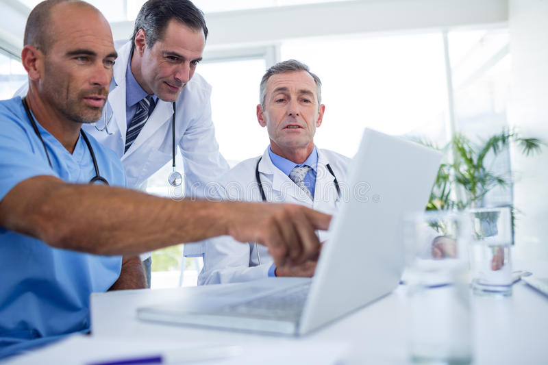 Doctor showing laptop pc to his colleagues. In medical office stock photos