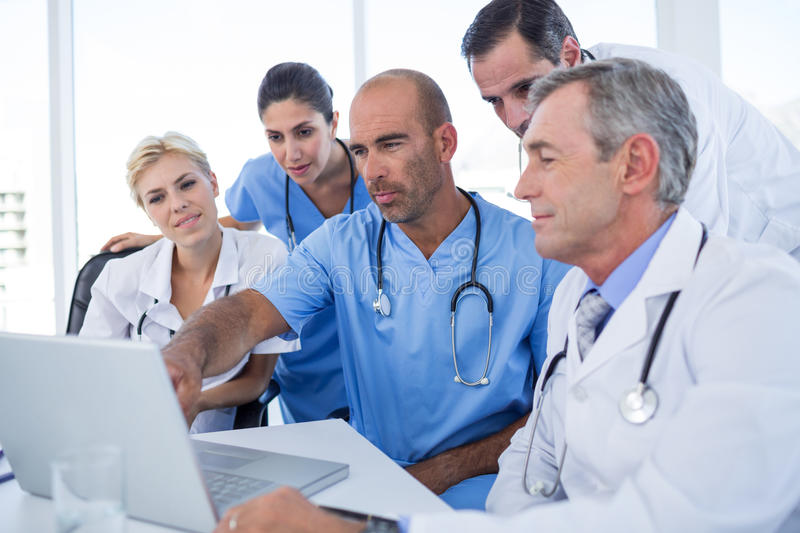 Doctor showing laptop pc to his colleagues. In medical office royalty free stock photo