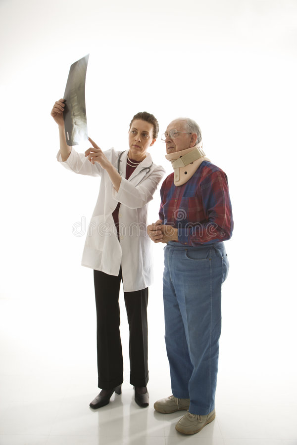 Doctor showing x-ray to elderly man in neck brace. royalty free stock photography