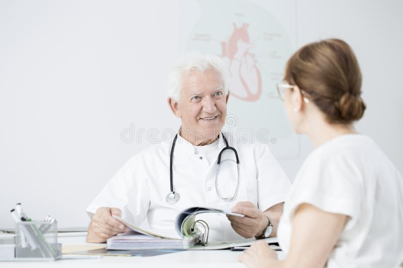 Doctor showing sanatorium brochures. Doctor in uniform showing sanatorium brochures to his patient with heart disease royalty free stock photos