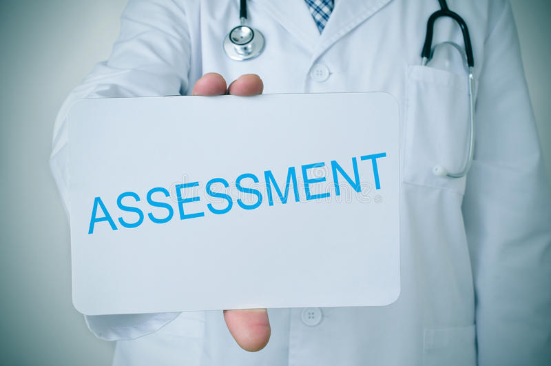 Doctor showing a signboard with the word assessment stock image