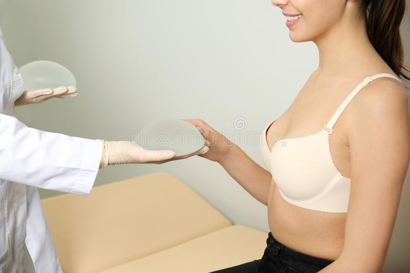 Doctor showing silicone implants for breast augmentation to patient in clinic, closeup. Cosmetic surgery stock photo