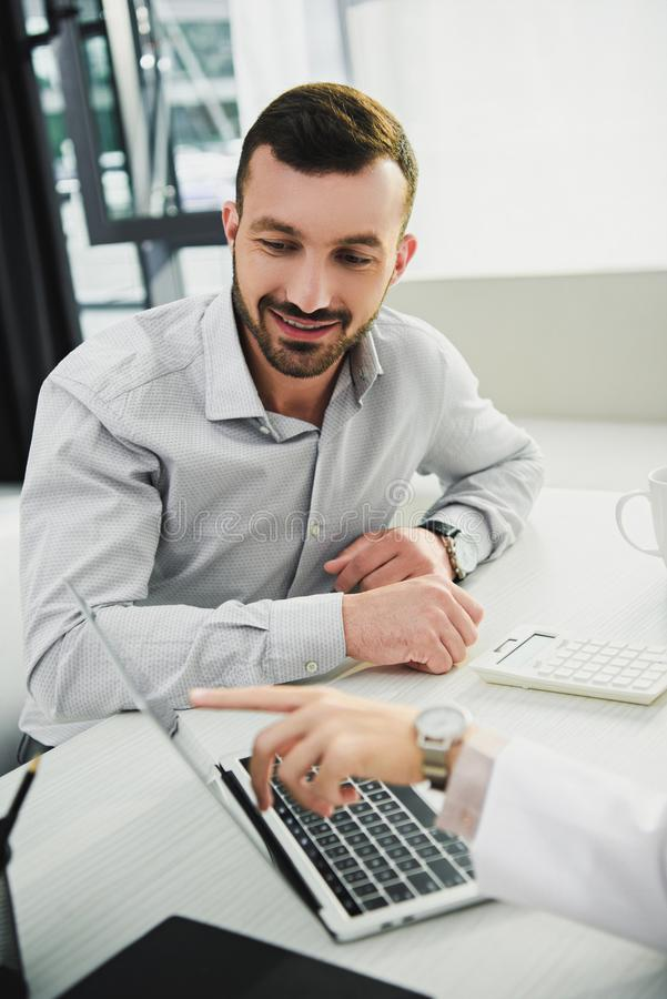 doctor showing something on laptop to male client royalty free stock photography