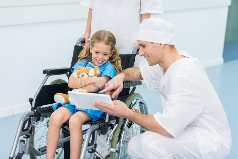 Doctor showing something on tablet to kid. On wheelchair royalty free stock photography