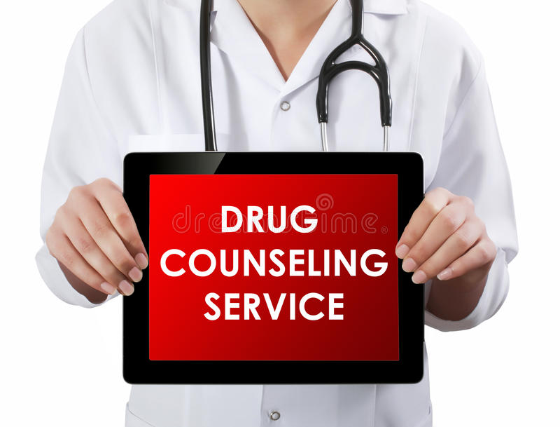 Doctor showing tablet with DRUG COUNSELING SERVICE text. stock photo