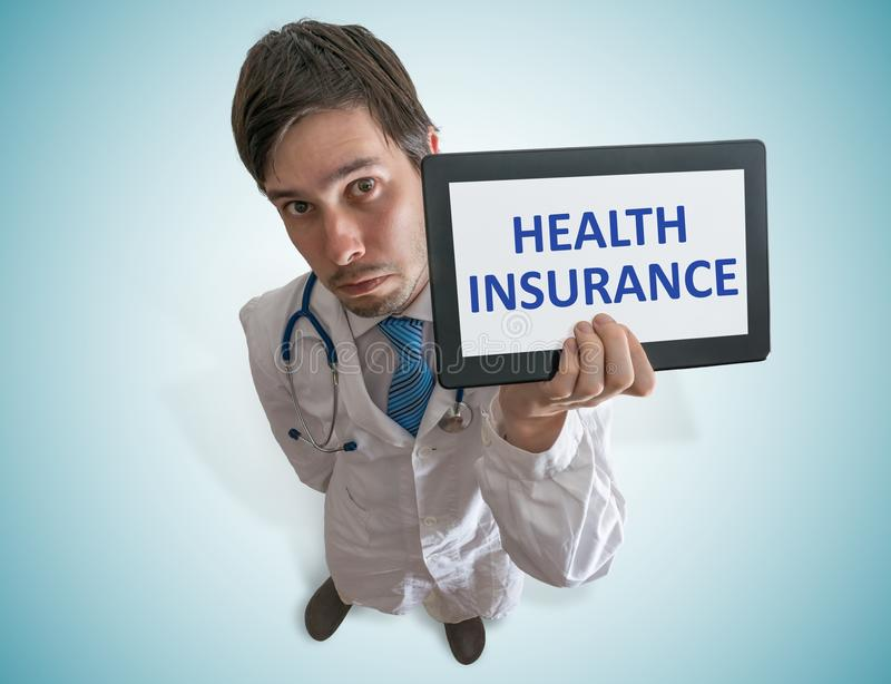 Doctor is showing tablet with health insurance text written. View from top stock photography