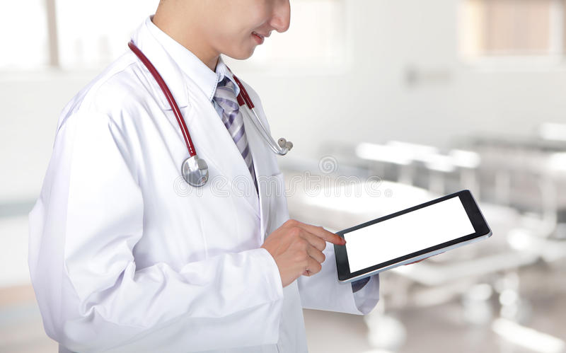 Doctor showing tablet pc in hospital. Doctor showing blank tablet pc in hospital, asian model royalty free stock images