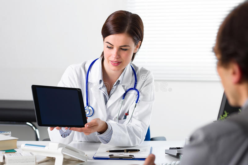 Doctor showing tablet to patient stock image