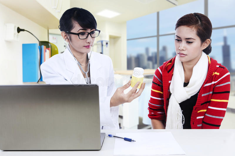 Download Doctor Showing Yellow Solution To Patient Stock Image - Image: 27169463