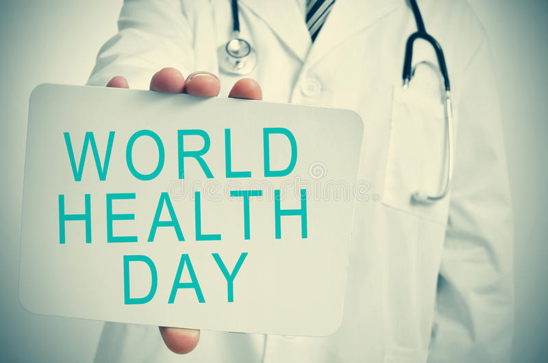 Doctor shows a signboard with the text world health day royalty free stock photos