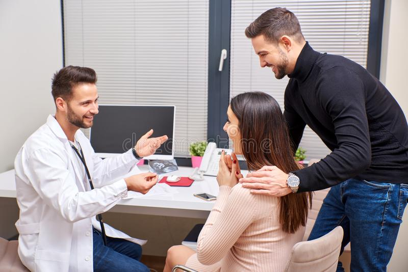 A doctor shows the ultrasound picture to the couple. A handsome male doctor shows ultrasound picture to the young pregnant couple stock images