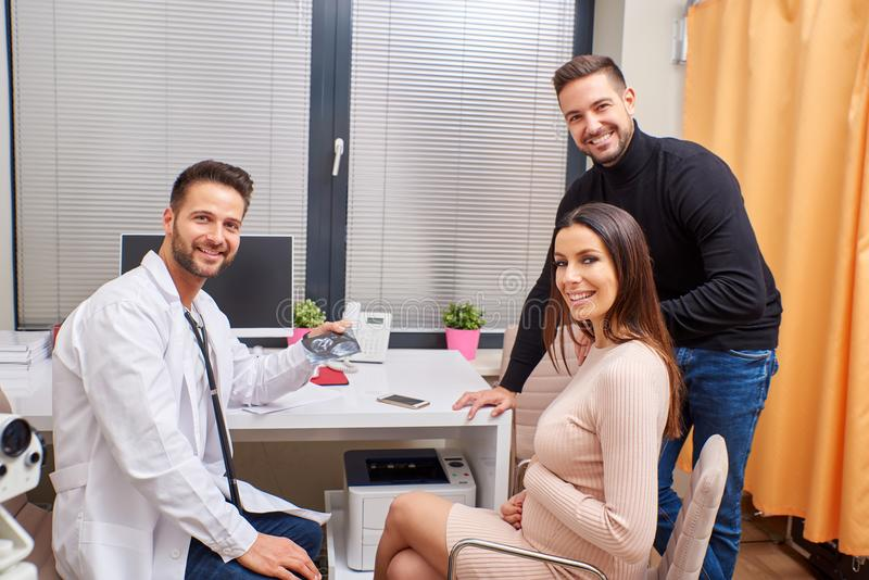 A doctor shows the ultrasound picture to the couple. A handsome male doctor shows ultrasound picture to the young pregnant couple stock photography