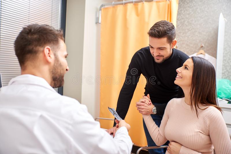A doctor shows the ultrasound picture to the couple. A handsome male doctor shows ultrasound picture to the young pregnant couple royalty free stock images