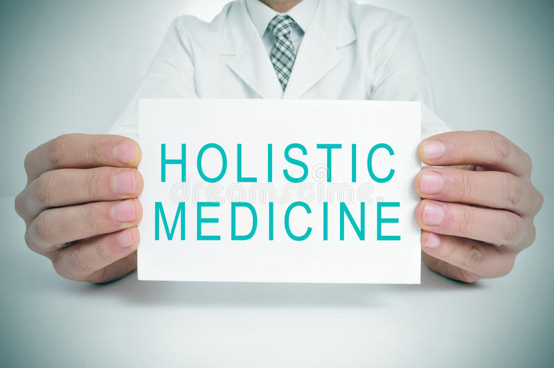 Doctor with a signboard with the text holistic medicine. A doctor showing a signboard with the text holistic medicine written in it royalty free stock photos