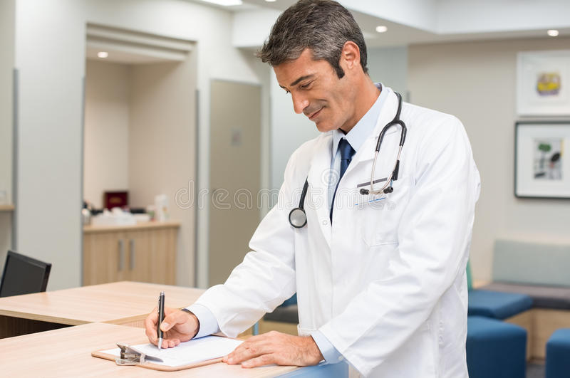 Doctor signing form stock photos