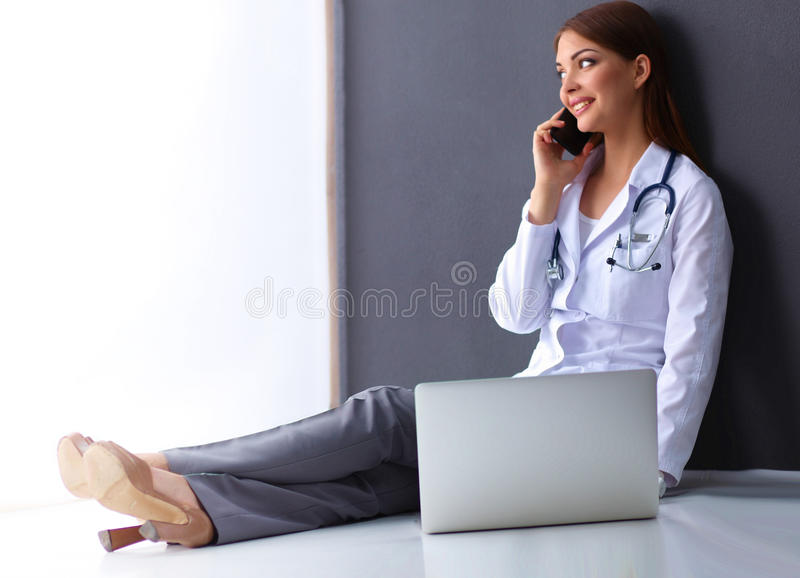 Doctor sitting the floor near wall with laptop and talking on phone. Doctor woman sitting on the floor near wall with laptop and talking on the phone stock photography