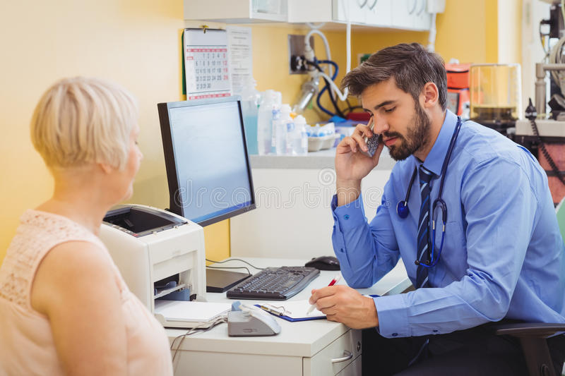 Doctor sitting at his desk and talking on phone. At the hospital stock photos