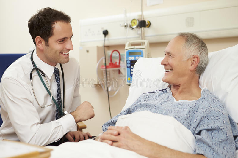 Doctor Sitting By Male Patient's Bed In Hospital stock photos