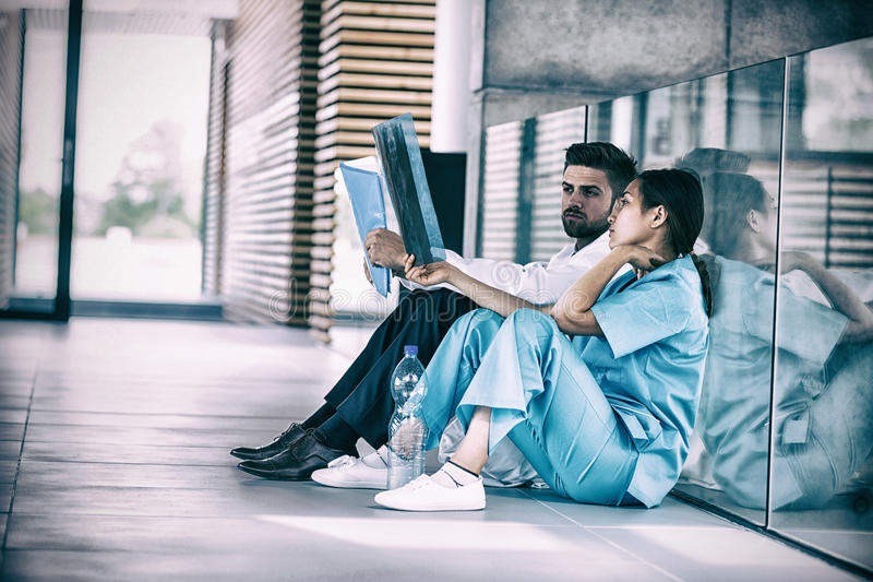 Doctor sitting by nurse on floor examining X-ray report. In hospital corridor royalty free stock photo