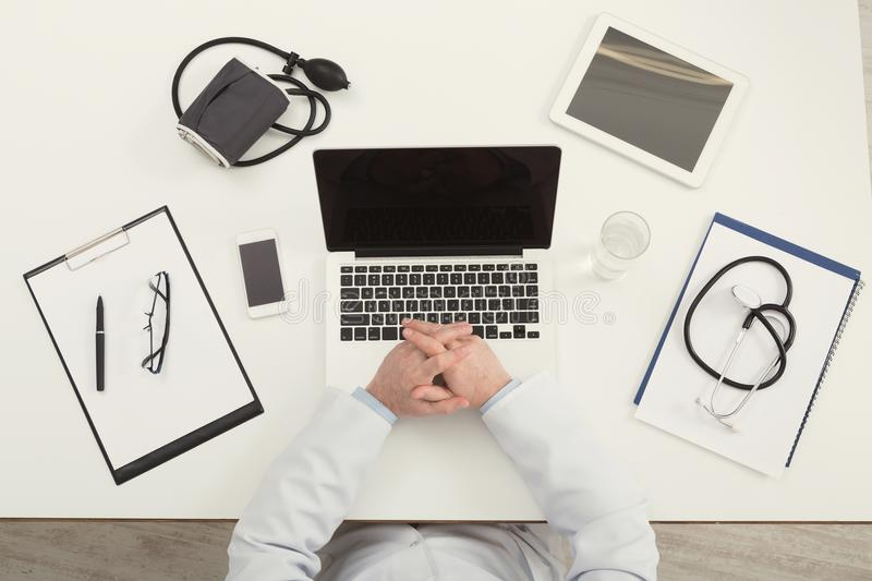 Doctor sitting at office desk, top view stock photo