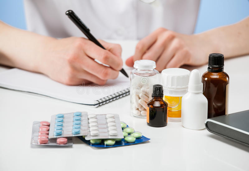 Doctor sitting at the table and writing among drugs royalty free stock photo