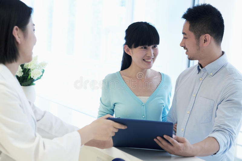 Doctor and smiling couple standing by the counter in the hospital looking at medical record royalty free stock photography