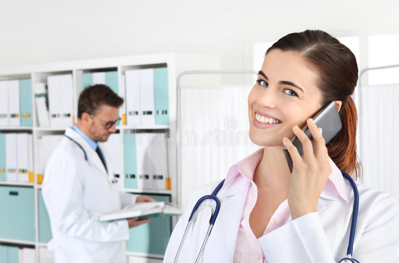 Doctor smiling on the phone, concept of medical booking. Doctor smiling on the smart phone, concept of medical booking royalty free stock images