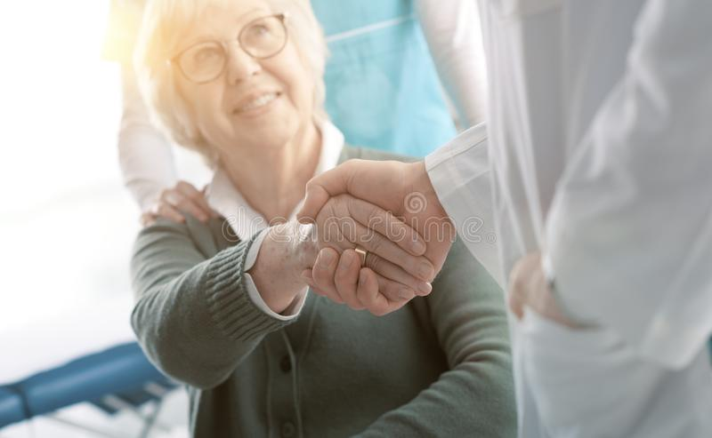 Doctor and senior patient shaking hands in the office stock photo