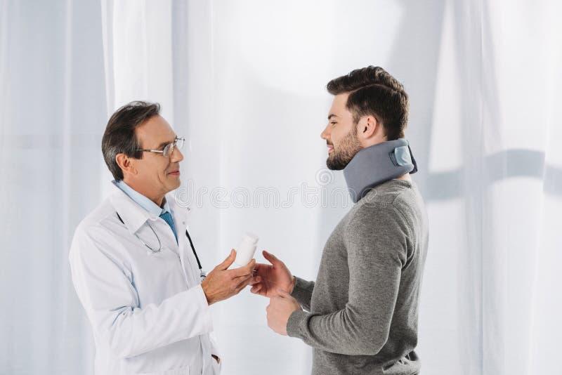 Doctor som ger pills till tålmodig royaltyfri fotografi