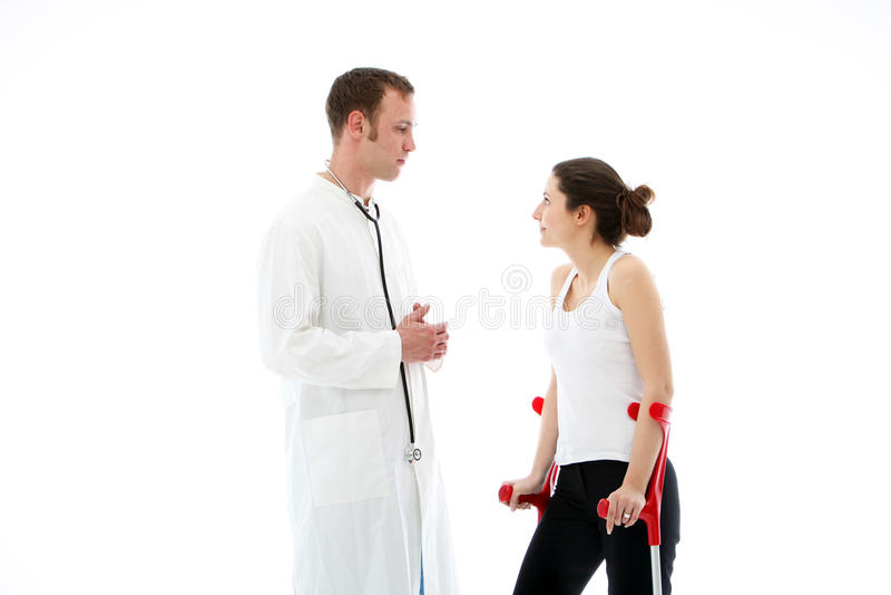 Doctor som talar till kvinnlig tålmodig på kryckor royaltyfria bilder