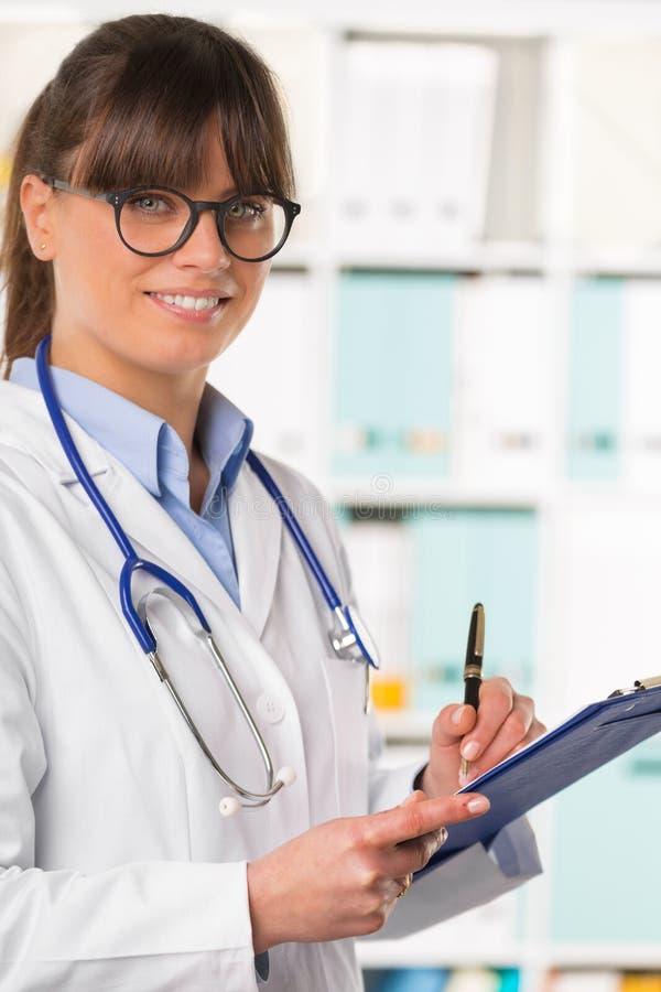 Doctor sonriente de la mujer con el tablero y la pluma fotografía de archivo libre de regalías