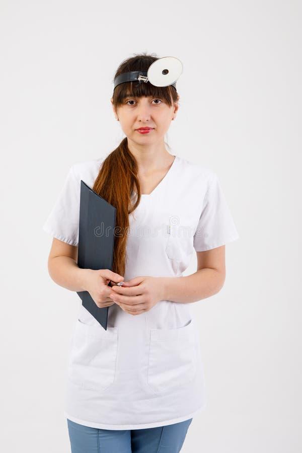 Doctor sonriente del otorrinolaring?logo del retrato con el espejo m?dico en la cabeza aislada en blanco fotos de archivo libres de regalías