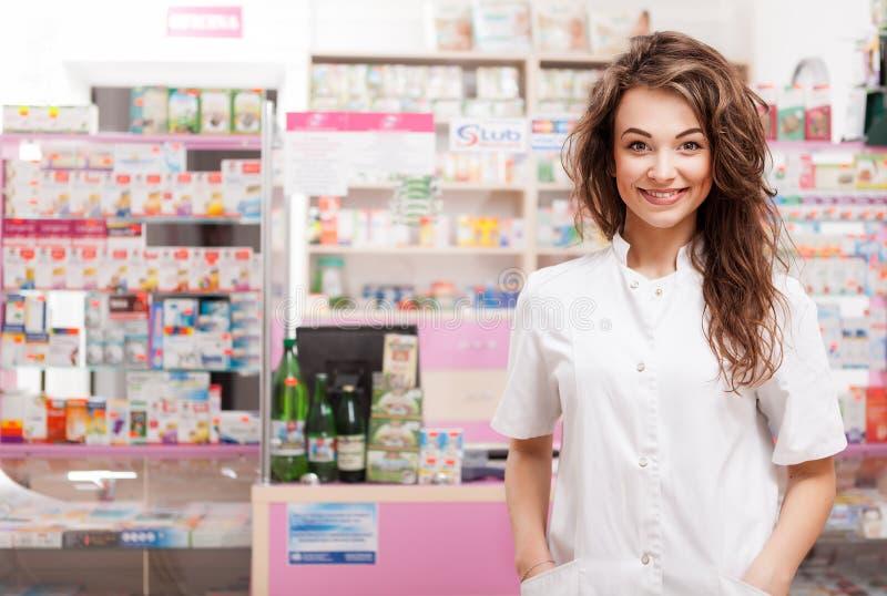 Doctor sonriente delante del escritorio de la farmacia foto de archivo libre de regalías