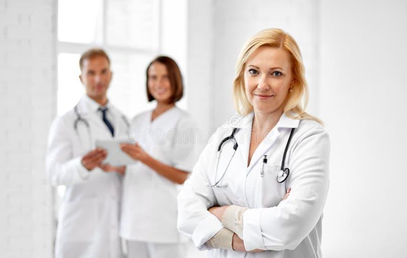 Doctor sonriente en la capa blanca en el hospital imagenes de archivo
