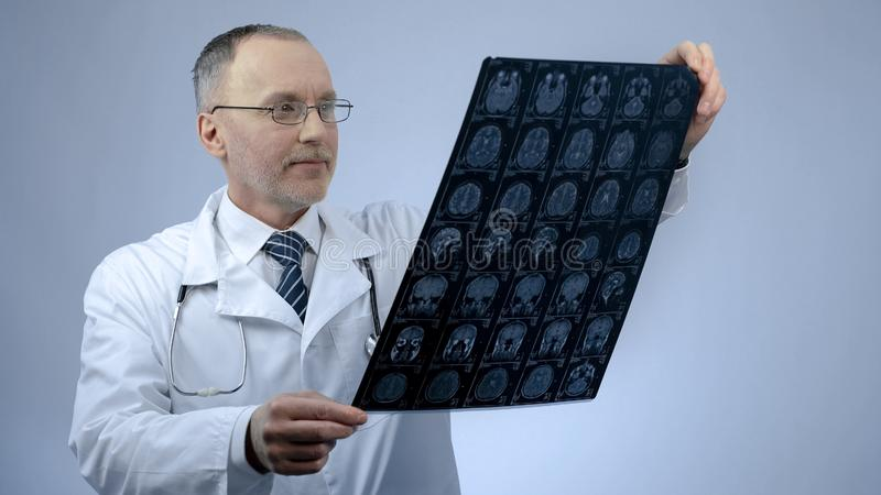 Doctor sonriente feliz que comprueba la exploración de cerebro de MRI, satisfecha con resultados de tratamiento fotos de archivo