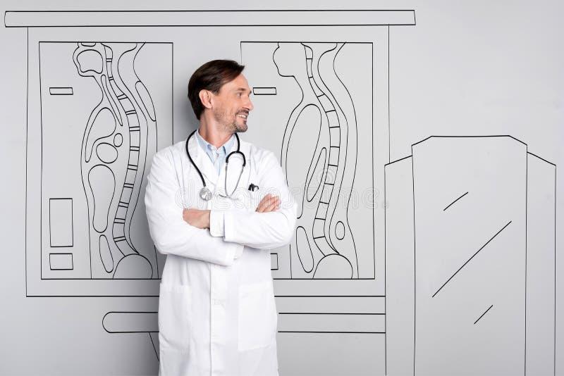 Doctor sonriente feliz que se coloca en el hospital fotografía de archivo