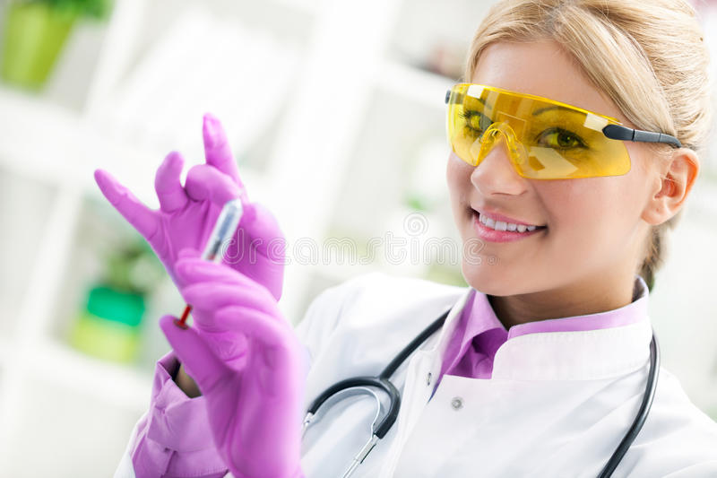 Doctor sonriente joven que prepara una inyección imagen de archivo libre de regalías