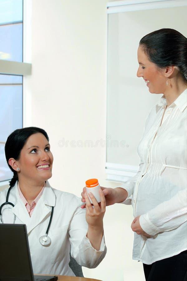 Doctor sonriente que da las vitaminas a una mujer embarazada imagenes de archivo