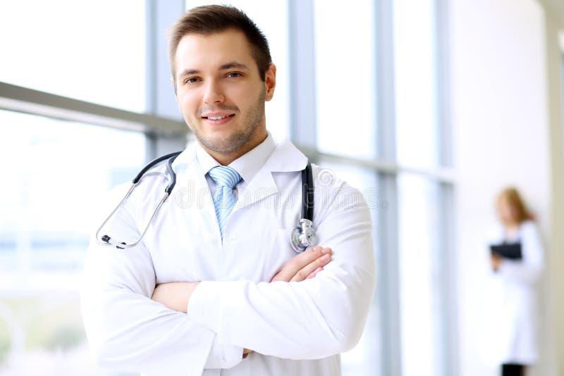 Doctor sonriente que espera a su equipo mientras que se coloca vertical fotografía de archivo