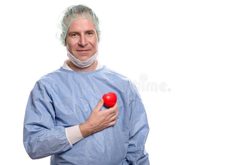 Doctor sonriente que lleva a cabo un corazón rojo brillante fotos de archivo libres de regalías