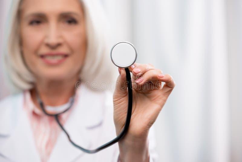 Doctor sonriente que sostiene el estetoscopio disponible fotografía de archivo libre de regalías