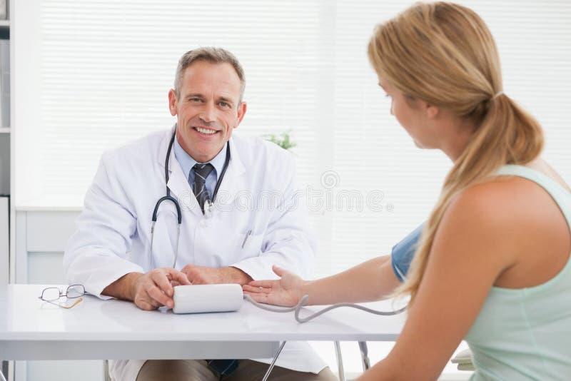 Doctor sonriente que toma a pacientes la presión arterial foto de archivo libre de regalías