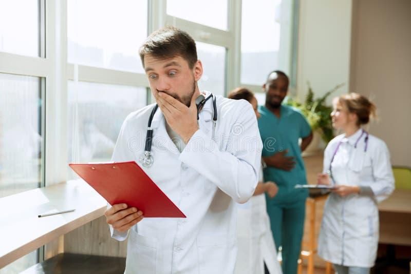 Doctor sorprendido hermoso sobre fondo del hospital imagenes de archivo