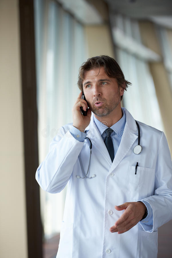 Doctor speaking on cellphone. Handsome doctor speaking on cellphone at modern hospital indoors royalty free stock images